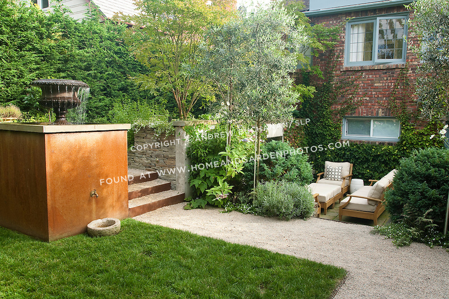 A small lawn with water feature and a cozy conversation area offer two distinct areas in this multi-level Seattle backyard.  Design by Scot Eckley, Inc.
