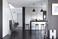 The monochrome kitchen is furnished with a bar in polished metal and benefits from a wall of fitted cupboards