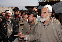 Muhammad Sidiq Sheikh (right), 65, says the only source of water for Dardpora is a small stream which dries up during winters. A crowd of men tells a reporter about their situation. Dardpora, Kashmir, India. © Fredrik Naumann/Felix Features
