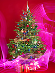 Decorated Christmas tree with purple lighting effects around it