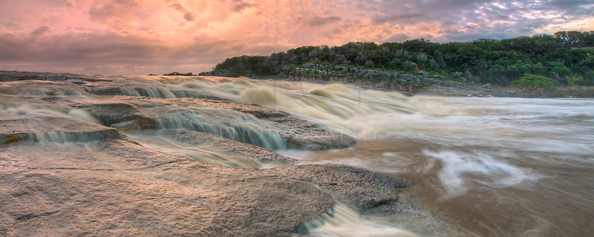This panorama of the Pedernales River in the Texas Hill Country was taken in May of 2015 after rains had fallen for weeks. The river was high and over its banks. The sky was glowing a pinkish/orange hue at sunrise, and the landscape was surreal