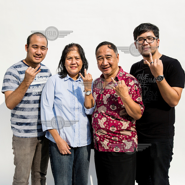A family flash a two fingered sign, symbolising Indonesian presidential candidate Jokowi's candidacy number after they cast their votes at a polling station in Jakarta.