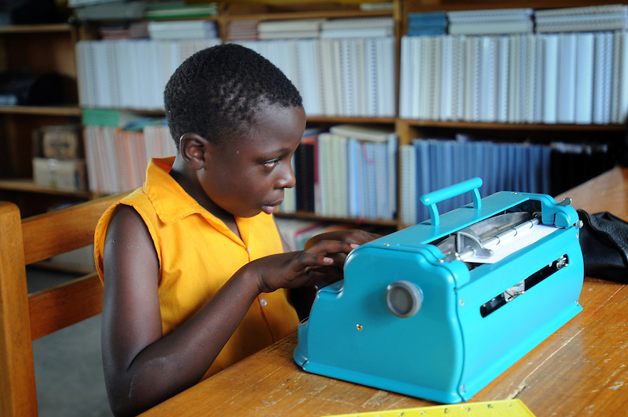 BRAILLE BIBLE CASE STUDIES AT MARTON NKOYOYO SCHOOL, KAMPALA, UGANDA. JOSELINE NAMUBIRU, 10, USING A BRAILLE MACHINE.