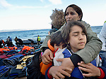 A mother hugs her children on a beach near Molyvos, on the Greek island of Lesbos, on October 31, 2015.  The family, part of a boatful of refugees that arrived from Turkey, were received by local and international volunteers, then proceeded on their way toward western Europe. The boat was provided by Turkish traffickers to whom the refugees paid huge sums to arrive in Greece.