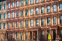 Attached row of brownstone buildings on Lenox Avenue in the Harlem neighborhood of New York on Friday, February 28, 2014. (© Richard B. Levine)