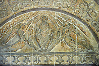 Tympanum of the south door of the 12the century  church of St Peter & St Paul depicting Chirst in Majest, Pantocrator, with flying angels each side holding up the Mandorla or aureol he is sitting in. This is very typical of Eastern Roman or Byzantine art and the geometric designs suggest this is Norman art of the 12th century rebuilding  of Malmesbury Abbey, Wiltshire, England