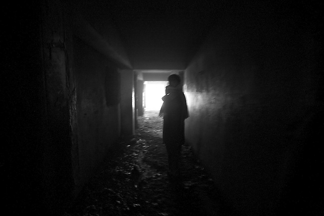 A man leads a visitor down a darkened corridor inside the ruins of the former Soviet Cultural Center in Kabul, Afghanistan. Afghanistan produces more than 90 percent of the world's opium--from which heroin is derived--and its cheap availability is wreaking havoc on a society already ravaged by 30 years of war. As many as 2,000 addicts gather each day to get high inside the derelict structure, which was  almost completely destroyed during the 1992-1994 civil war. Feb. 2, 2009.