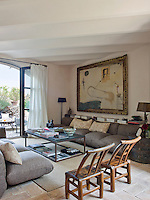 A pair of Chinese chairs at one end of the living room seating area sit opposite the French windows that open onto the courtyard
