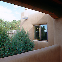 There is a fine view of the surrounding hills from the covered terrace of this contemporary adobe house