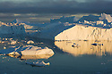 Large icebergs drifting in fiord, midnight, end of June, mid summer night; Disko Bay, Greenland