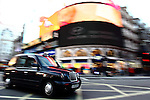 A black cab crosses the junction at Piccadilly Circus in London's West End.
