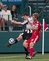 Rochester Rhinos midfielder Tyler Rosenlund (8) goes deep into the corner and crosses the ball as Chicago Fire defender Pari Pantazopoulos (24) pressures. In a Third Round U.S. Open Cup match, the Chicago Fire defeated the Rochester Rhinos, 1-0, at Sahlens Stadium on June 28, 2011.