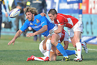 Mirco Bergamasco of Italy (L) is tackled by two Welsh players during the rugby match between Italy and Wales for the 6 Nations Championship 2011 at the Stadio Flaminio in Rome on February 26, 2011.