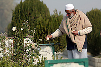 The caretaker of Iddgah martyrs' cemetary  sprinkles flowers on a grave. Around a thousand peole have been buried in this cemetary alone since 1989, after being killed by Indian security forces. Srinagar,Kashmir, India. © Fredrik Naumann/Felix Features