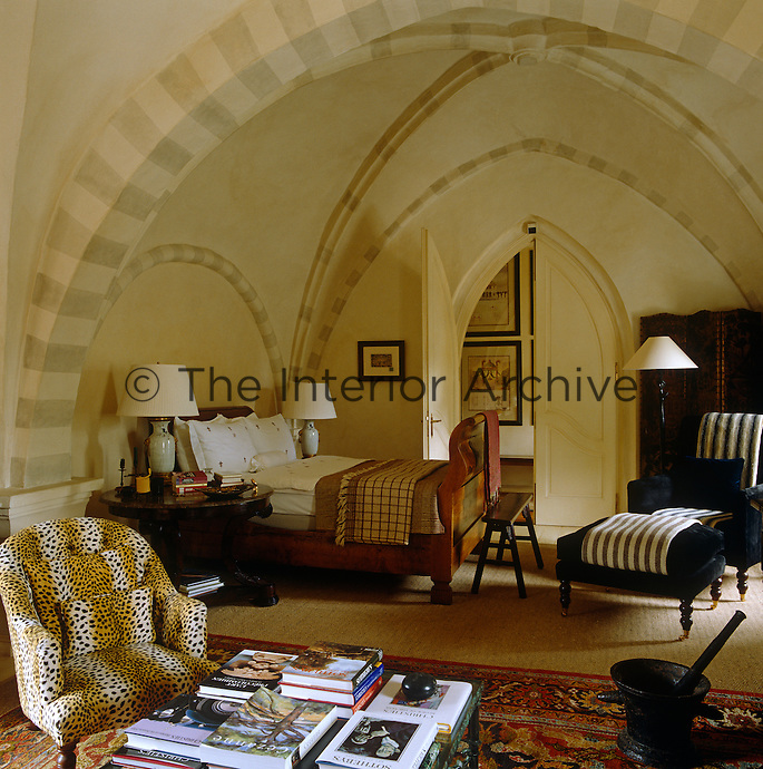 This vaulted bedroom is furnished with comfortable armchairs upholstered in striped and leopard print fabrics