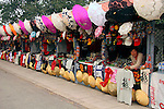 Asia, China, Beijing. A vendor touts a t-shirt in a row of Chinese tourist shops in Beijing.