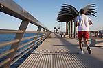 Man Jogging on the Harbour Pier Promenade Wall Walk in Alicante, Spain