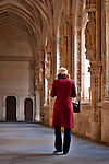 A woman in a red winter coat walking down the hall of the Monastery and Church of San Juan de los Reyes in Toledo, Spain