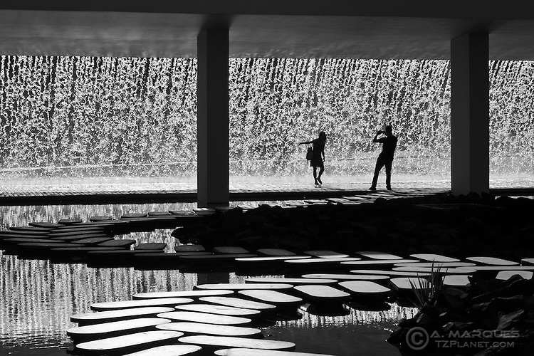 A girl modelling for her partner under the waterfall at Parque das Nações, Lisbon, Portugal. .Parque das Nações, the development originated after the Expo 98, has many examples of modern architecture, both in commercial and residential spaces. This area also features Europe's largest Oceanarium, restaurants, bars, event halls and permanent exhibit halls.  .Parque das Nações is located right next to the Tagus River (Rio Tejo) on the East of Lisbon.
