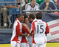 Toronto FC midfielder Matias Laba (20) celebrates his goal with teammates. In a Major League Soccer (MLS) match, Toronto FC (white/red) defeated the New England Revolution (blue), 1-0, at Gillette Stadium on August 4, 2013.