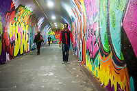 Travelers pass through the 900-foot long 191st Subway station connecting tunnel, newly decorated by artists hired by the New York City Dept. of Transportation on Thursday, May 21, 2015. The artists, COPE2, Queen Andrea, Nick Kuszyk, Cekis and Jessie Unterhalter and Katey Truhn were chosen in a competitive process by the DOT. The tunnel has recently received upgraded LED lighting and with the addition of the murals has been turned into an art gallery. (© Richard B. Levine)