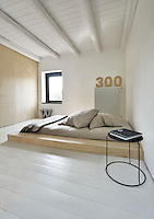 A simple white bedroom with a painted beamed ceiling and floorboards. A matress with a grey cover is set on a wooden plinth.