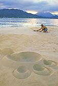 Sand sculpture artist Barry Peckham on one of moku lua islands of the coast of Lanikai, Windward Oahu