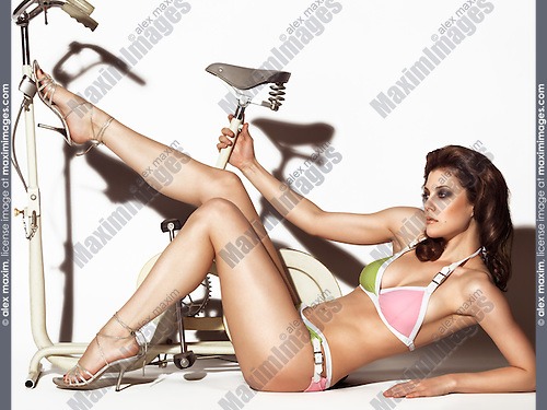 Young woman in a trendy swimsuit posing with a retro exercise bike. Edgy high fashion photo.