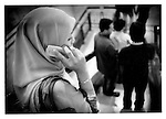 Young Malay woman, wearing hijab (tudong, in Malay) , talks on mobile telephone while descending escalator in KLCC shopping mall, Kuala Lumpur, Malaysia.