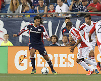 New England Revolution midfielder Juan Carlos Toja (7) on the attack.  In a Major League Soccer (MLS) match, Toronto FC (white/red) defeated the New England Revolution (blue), 1-0, at Gillette Stadium on August 4, 2013.