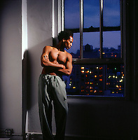 Shirtless African American man leaning against wall looking out window at night