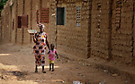A woman and girl walk along a street in Sonougouba, Mali, where the ACT Alliance has worked with local residents to encourage a sustainable economy, increase food security, and improve local governance.