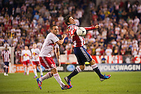 Jorge Villafaña (19) of CD Chivas USA plays the ball under pressure from Brandon Barklage (25) of the New York Red Bulls. The New York Red Bulls and CD Chivas USA played toa 1-1 tie during a Major League Soccer (MLS) match at Red Bull Arena in Harrison, NJ, on May 23, 2012.