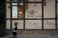 Poland, Krakow, Graffiti on wall, with boy walking past Kazimierz