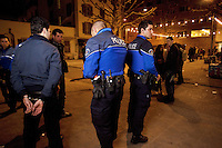 Switzerland. Geneva. A group of police officers arrest a man on the Volontaires place in front of the main entrance of &quot; L'Usine&quot;,  a wellknown place for nightlife. The handcuffed  man was arrested while selling drugs in the streets. The inmate is an arab man from the Maghreb area. The policemen are wearing a ballistic vest, bulletproof vest or bullet-resistant vest which is an item of personal armor that helps absorb the impact from knives, firearm-fired projectiles and shrapnel from explosions, and is worn on the torso. Soft vests are made from many layers of woven or laminated fibers and can be capable of protecting the wearer from small-caliber handgun and shotgun projectiles. 25.03.12 &copy; 2012 Didier Ruef..