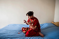 An afghan woman sits on the bed while polishing her nails at Kabul /Felix Features