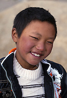 "May 1st, 2011_Shangri-La, Yunnan, China_ A young boy plays at his home in the tiny village of Rime, near the town of Zhongdian (or Shangri-La) in northern Yunnan province, China.  Several of these families take advantage of ""Home Stays,"" by opening their homes to visiting tourists.  Photographer: Daniel J. Groshong/The Hummingfish Foundation"