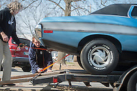 NWA Democrat-Gazette/ANTHONY REYES @NWATONYR<br /> Jerry Taplin (left), owner of Cars, Guitars and Antiques, and Jack Davis load a 1972 Ford Gran Torino Friday, Feb. 10, 2017 onto a trailer near his shop in downtown Bentonville. Tapin plans on trading the Torino for a 1946 Chrysler New Yorker.
