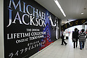 May 12, 2010 - Tokyo, Japan - Visitors walk pass a 'Michael Jackson - The official Lifetime Collection' exhibition poster, in a hall at the foot of Tokyo Tower, Tokyo, Japan, on May 12, 2010. More than 280 items of Michael Jackson memorabilia including crystal-studded gloves and favorite 1967 Rolls Royce are on display until July 4.  (c) MICHAEL JACKSON ESTATE