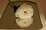 A white rose lays on an antique mirror.