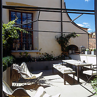 A large metal trellis that echoes the structure of the table has been built over the terrace for the vines to grow along