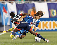 Players get tangled as Philadelphia Union midfielder Gabriel Farfan (15) dribbles by New England Revolution midfielder Clyde Simms (19). In a Major League Soccer (MLS) match, the New England Revolution tied Philadelphia Union, 0-0, at Gillette Stadium on September 1, 2012.