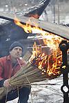 Foto: VidiPhoto<br /> <br /> ARNHEM - Ondanks waarschuwingen van Rijkswaterstaat om niet te weg op te gaan zaterdag in verband met winterse omstandigheden, trokken veel gezinnen er op uit om te genieten van de laatste dag van de Kerstvakantie. Het Nederlands Openluchtmuseum in Arnhem zorgde zaterdag voor dubbele sfeer, dankzij de sneeuwval. Bij tal van vuurtonnen en houtvuren konden bezoekers en vrijwilligers zich opwarmen. De winteropenstelling van het park met tal van activiteiten blijkt een enorm succes. Er zijn tot nu toe al meer bezoekers dan andere jaren. Eind volgende week gaan de deuren dicht tot komend voorjaar. Foto: Een prettig klusje met de kou: het verhitten van eikenplanken, zodat de krom trekken voor de bouw van een zogenoemde kubboot.