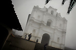 GUATEMALA  --  FEBRUARY 6, 2007:   People walk past the church on a foggy day in Chaul on February 6, 2007 in Guatemala.  (PHOTOGRAPH BY MICHAEL NAGLE)