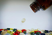 An assortment of coloured pills and capsules pouring out of a bottle. Royalty Free