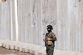 KIRKUK, IRAQ:  An Iraqi Army soldier stands guard near a T-wall in Kirkuk...Security is tightened in the volatile Iraqi city of Kirkuk the day before the national elections.  Kirkuk is home to Kurds, Arabs, and Turkmen and has been so violently divided that the city could not participate in the 2005 elections.