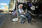 A man relaxes in a camp in Managua of some 3,000 former banana workers who have been poisoned by Nemagon (dibromochloropropane). Camped out across the street from the Nicaraguan National Assembly, the workers are pressuring the government to provide health care and support their legal actions against US companies which manufactured and used the pesticide. Nemagon is considered a risk factor for cancer, kidney failure, acute respiratory disease, heart attack, sterility, muscular atrophy, skin complaints, and other health problems. The tall building in the rear is the National Assembly.