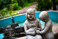 A broken statue of girls holding a rabbit, in front of an empty fountain, at the Havana Zoo, Havana, Cuba, 12 February 2011. The largest and the oldest zoo in Cuba (founded in 1939) is located in a centric neighborhood of the capital. Since the 1990s Cuba struggles with chronic economic crisis and therefore the strong marks of rundown and lack of sources are evident within the whole zoological garden. A lot of cages are empty and out of use for long time, the remaining animals are captured in poorly maintained pits. Concrete enclosures have no vegetation, all facilities are unkept. The food supply is often inadequate and visitors throw junkfood to the animals because there are no zookeepers around.