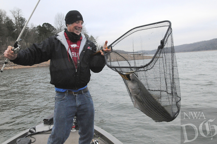 NWA Democrat-Gazette/FLIP PUTTHOFF <br /> Brad Wiegmann of the Springdale catches a big striped bass Feb. 24 2017 at Beaver Lake. Gulls feeding on shad often indicate schools of stripers and other game fish feeding below. Wiegmann used an electronic depth finder to catch this striper.