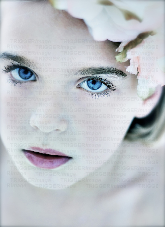 Close up of young girls face with blue eyes looking at camera